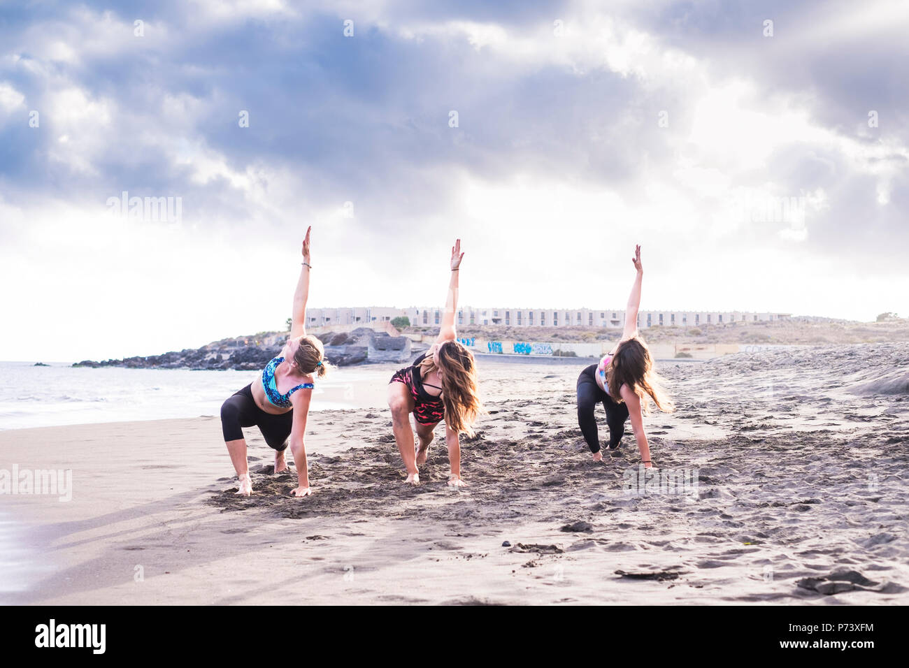 Grupo de tres personas amigas hacer ejercicios de equilibrio y fuerza como yoga y pilates en la playa. Costa y pintoresco lugar de arena durante beauti Imagen De Stock