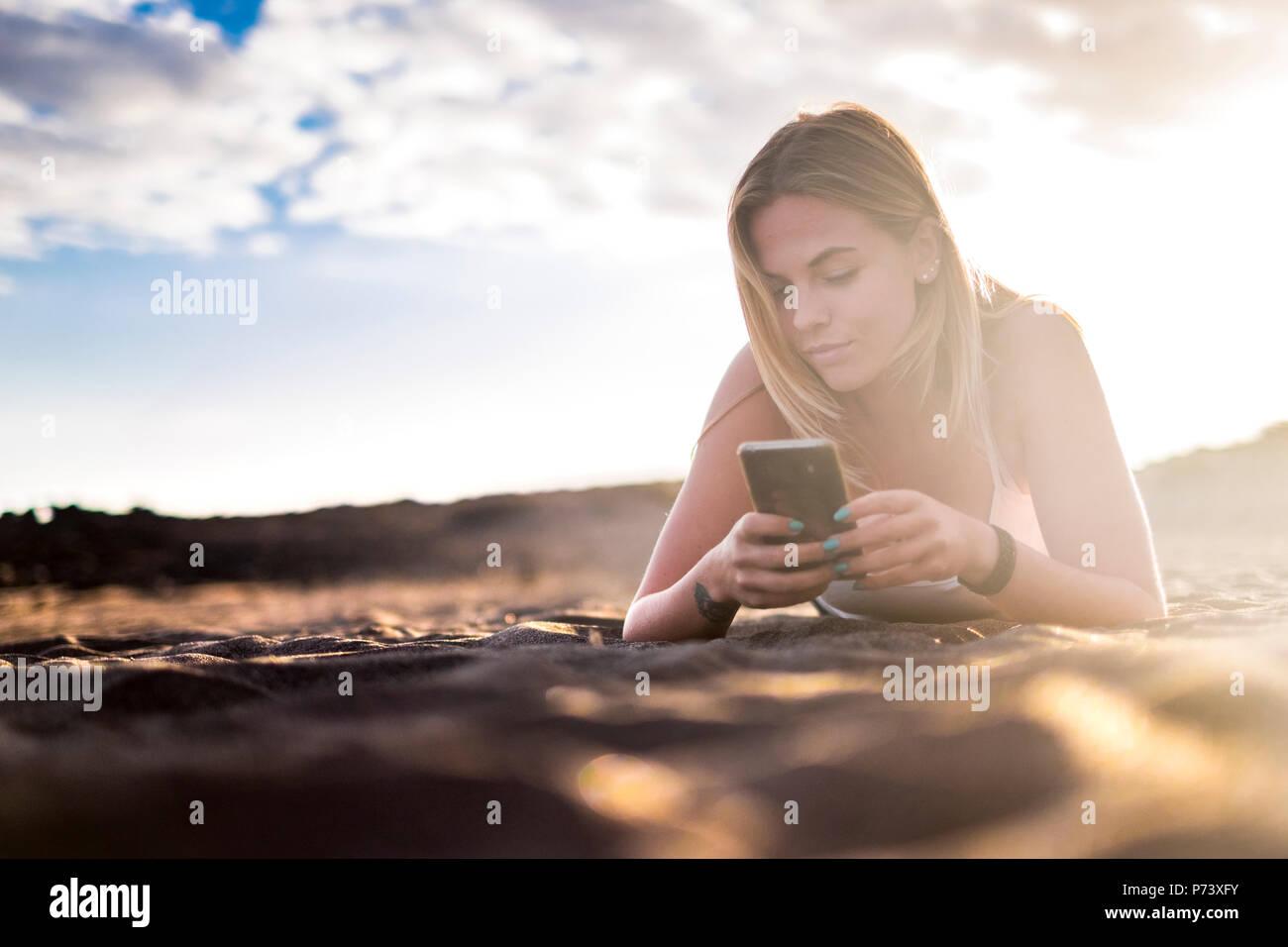 Hermosa joven mujer rubia sentar en la playa de vacaciones La actividad de ocio y estilo de vida utilizando un smartphone para controlar los medios de comunicación social y el uso de interne Imagen De Stock