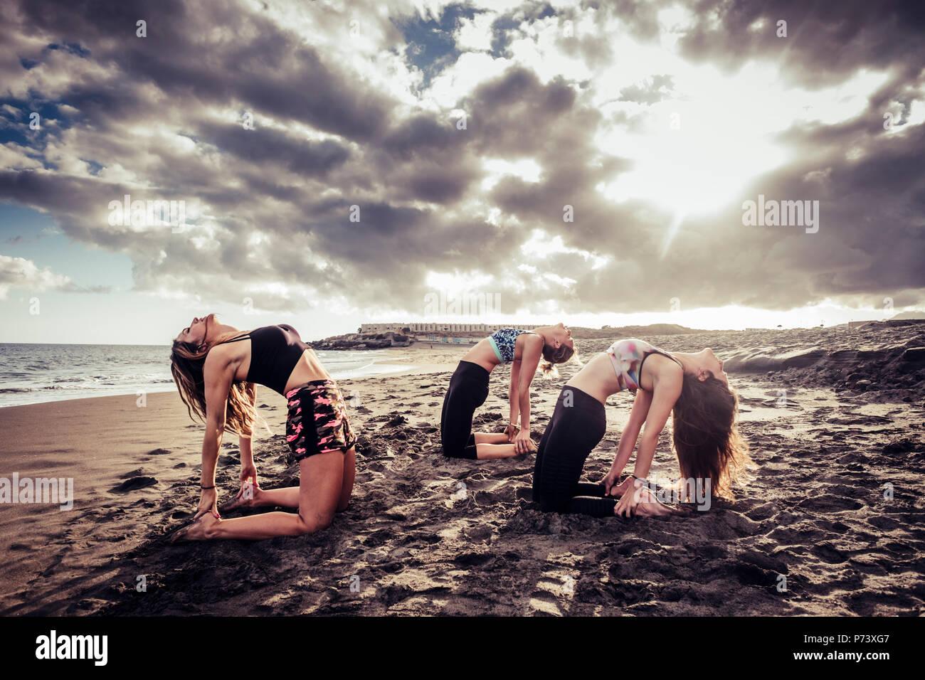 Captura escénica con tres jóvenes hermosas modelos señoras haciendo yoga y pilates en la playa en la arena. Las nubes y la luz del sol durante su increíble Foto de stock