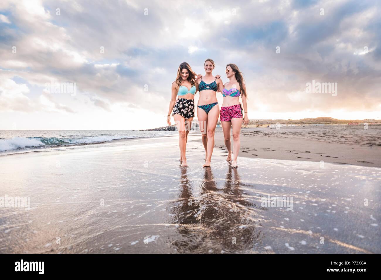 Tres bellas damas alegres jóvenes mujeres caminar en amistad y tener un buen tiempo juntos. vacaciones y Pueblo Caucasiano disfrutando de una felicidad. Imagen De Stock