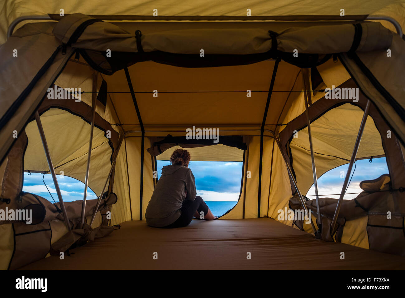 Lonely independiente fuerte mujer de mediana edad sentir la naturaleza al aire libre en una tienda de campaña en el techo del coche. viajes, vida y estilo wanderlust concepto para hermoso Imagen De Stock