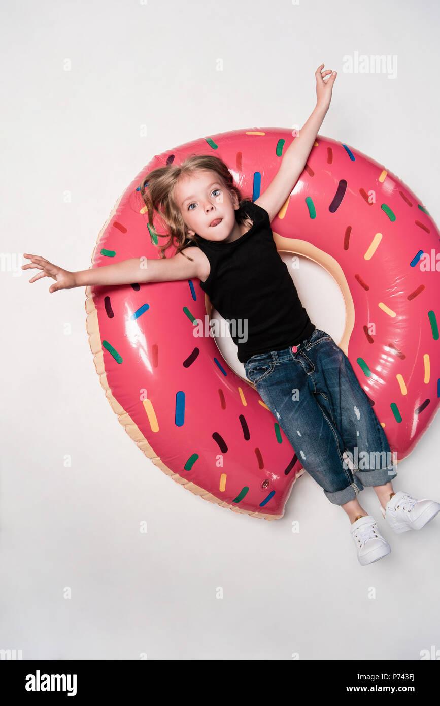 Niña descansa sobre la natación tubo en forma de rosquilla Imagen De Stock