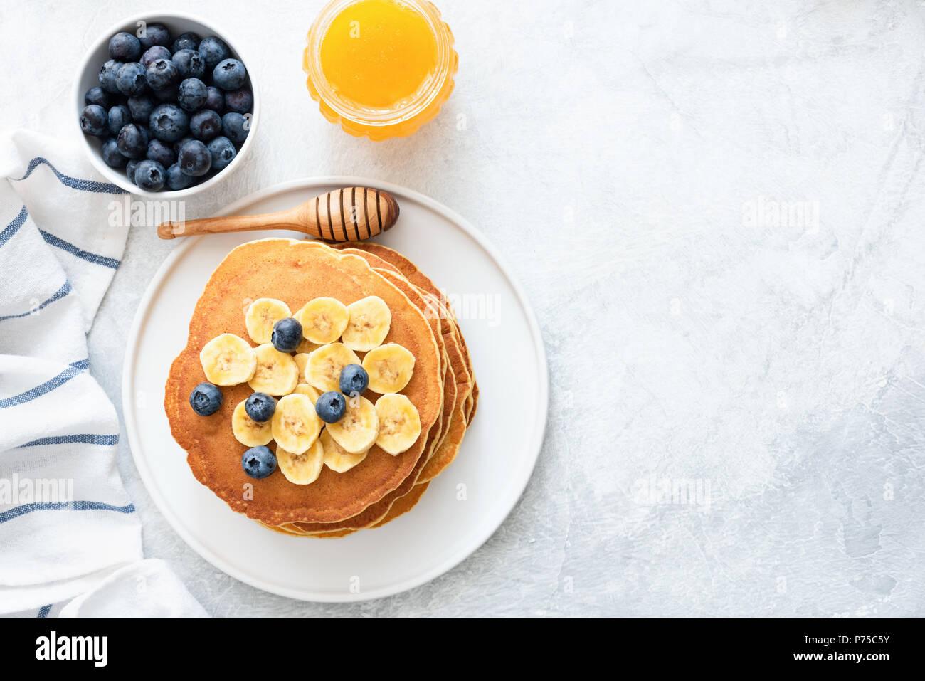 Tortitas de suero de leche con plátano, arándanos y miel sobre antecedentes concretos. Vista superior y espacio para copiar texto. Vista superior de tortitas con bayas en Foto de stock