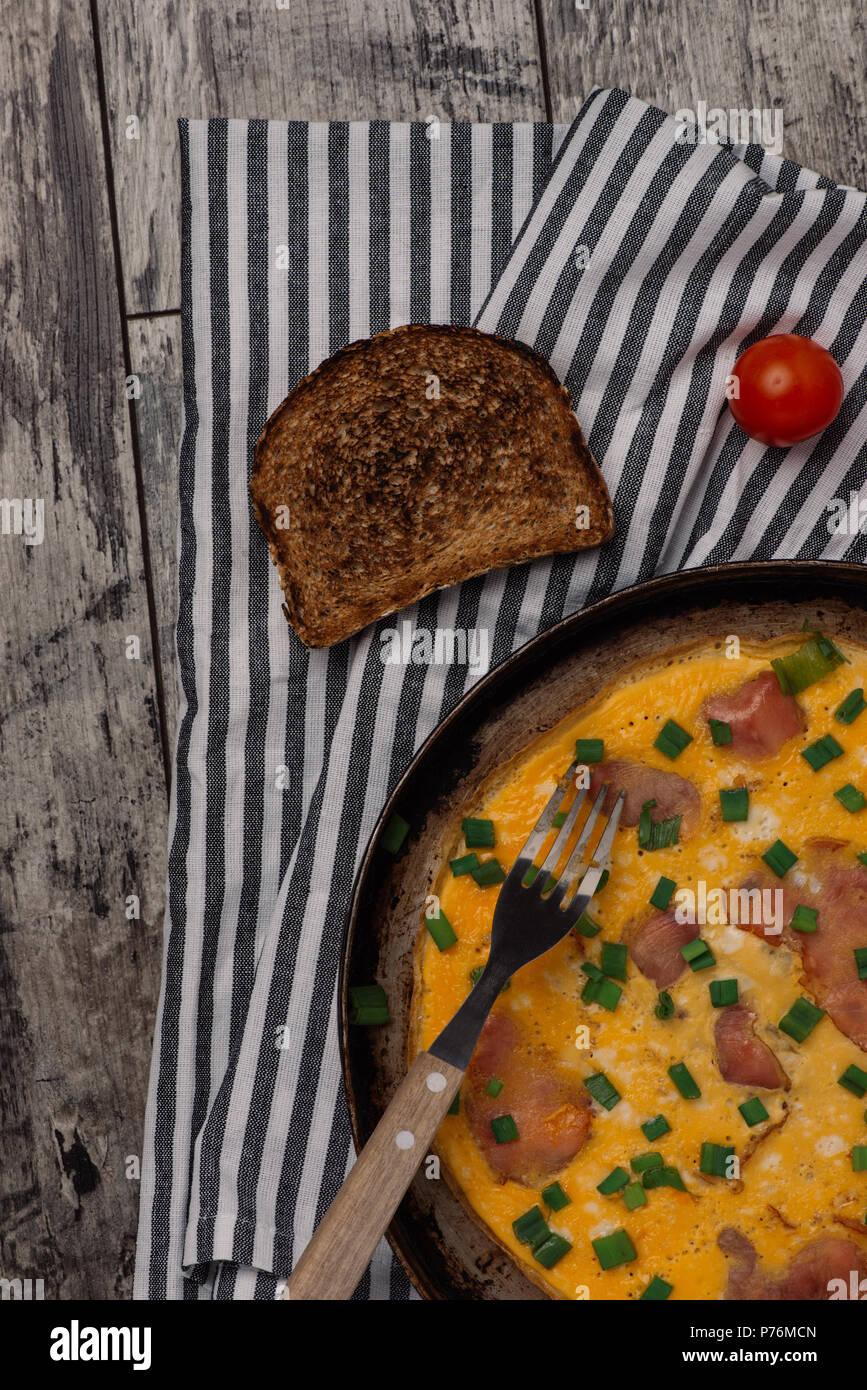 Primer plano de tortilla con jamón en la antigua placa rústica y cebolleta picada. Fotografiado desde arriba sobre la mesa rústica de madera antigua. Imagen De Stock