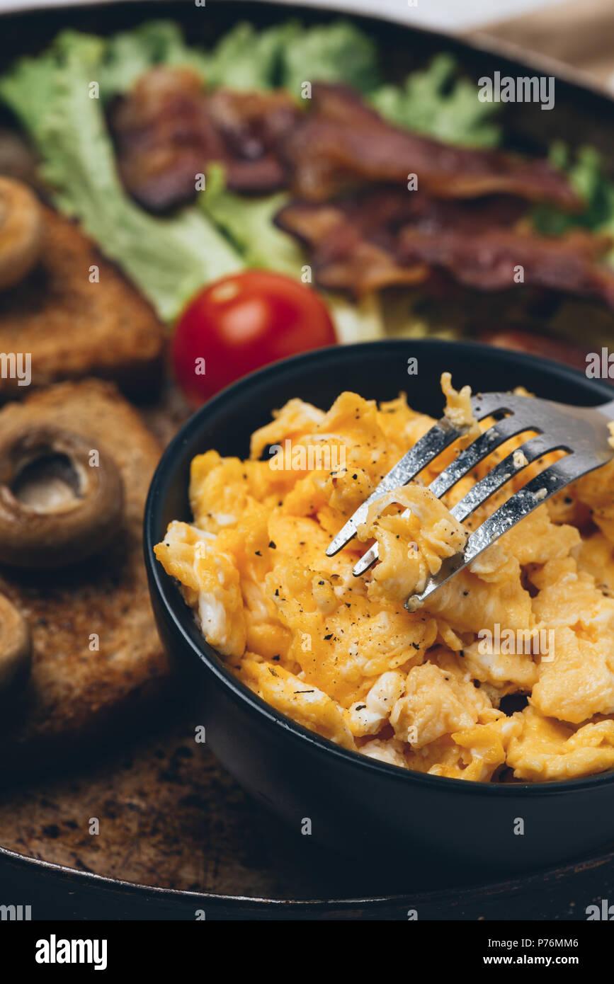Cerrar shot de sabroso y fresco, comida tradicional con tostadas, huevos revueltos, bacon frito, champiñones, ensalada verde y tomates cherry. Imagen De Stock
