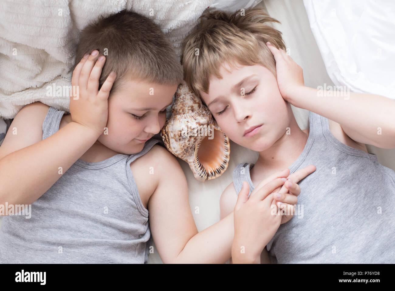 Hermanos - una mañana perezosa en la cama, la ropa de cama. Diversión y descanso, relax, perezoso Domingo Imagen De Stock