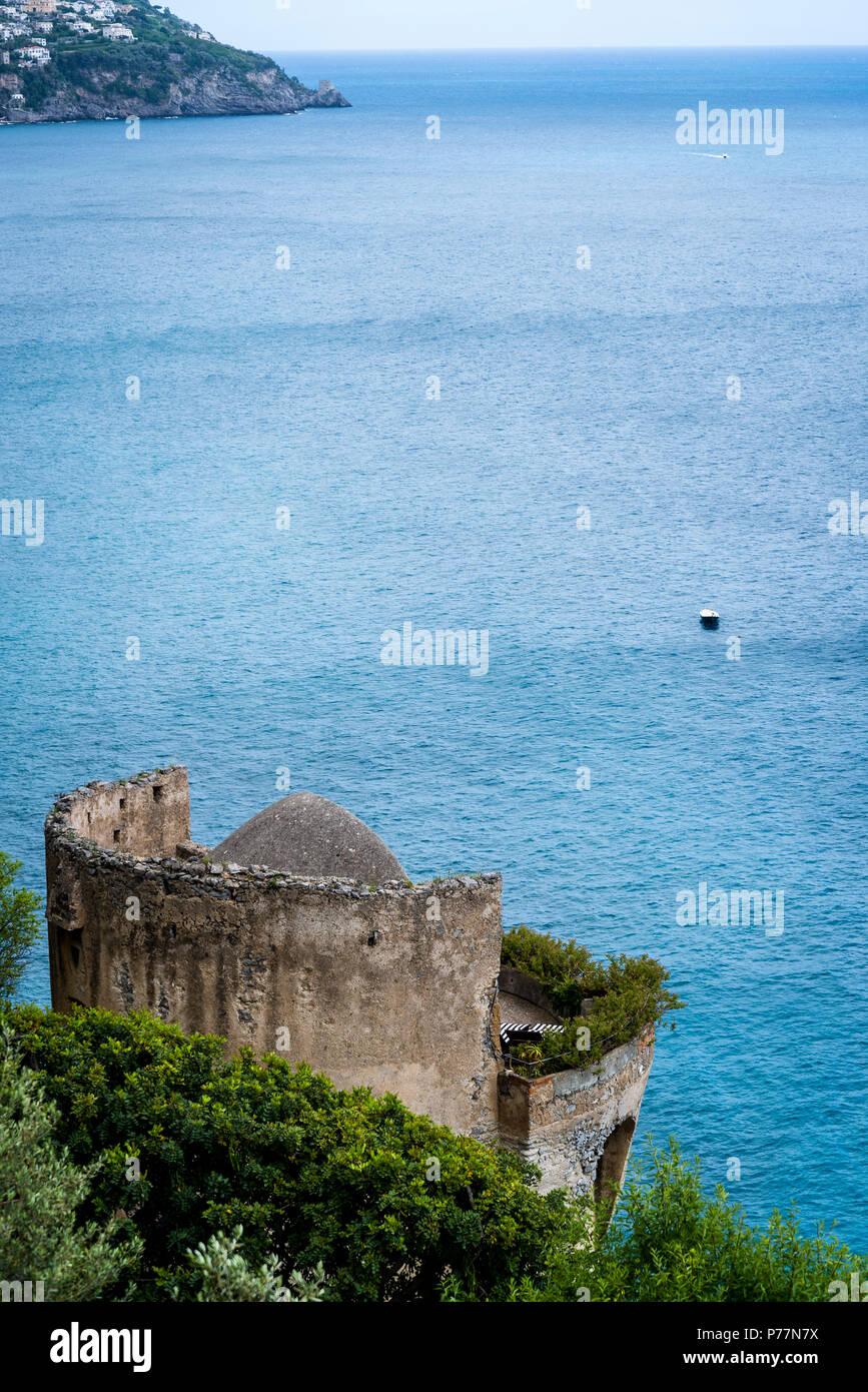 Positano, un pueblo al lado del acantilado, en la costa de Amalfi, antigua torre de vigilancia de piedra junto al mar, Italia Imagen De Stock