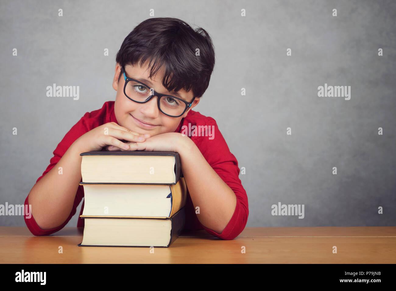 Niñito sonriente apoyado en libros sobre una mesa Imagen De Stock