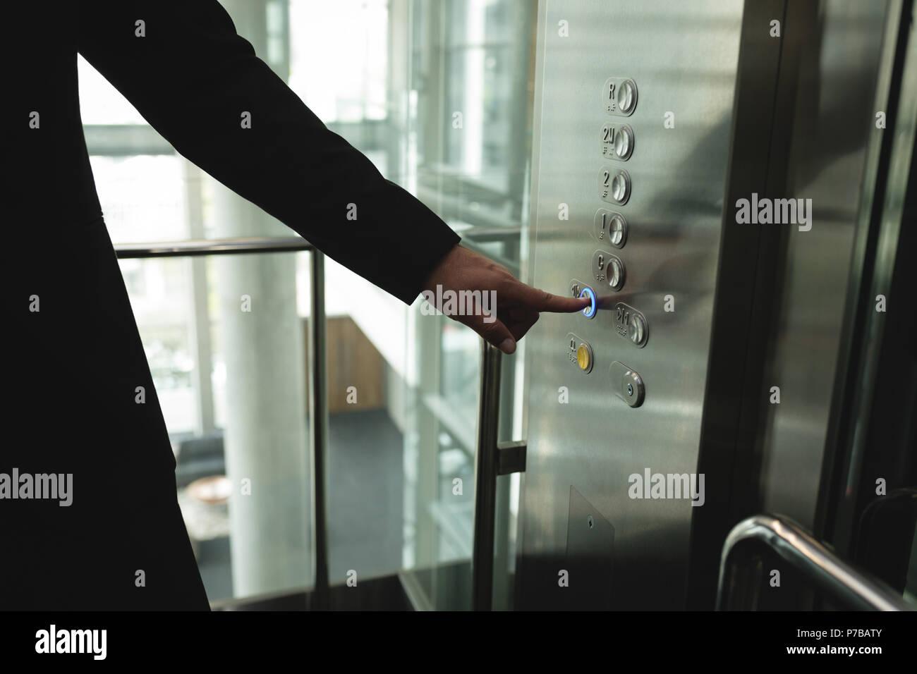 Empresario pulsando un botón en el ascensor Foto de stock