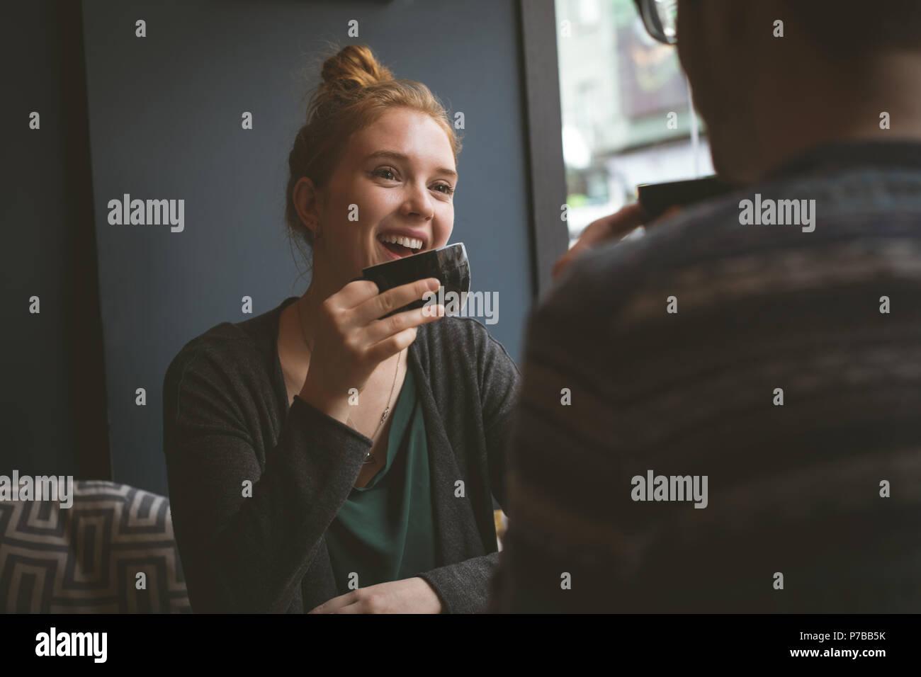 Pareja sonriente tomando café en la cafetería Imagen De Stock