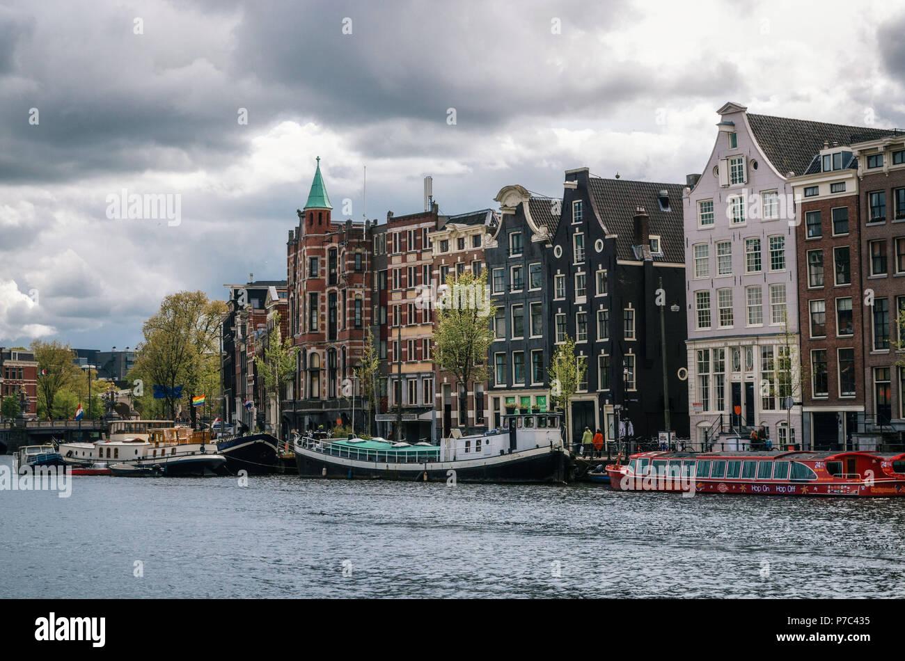 Amsterdam, Holanda - 27 de abril, 2017: Casas flotantes y viviendo barcazas en Binnenamstel canal contra casas de típica holandesa con pabellón de Países Bajos y Foto de stock
