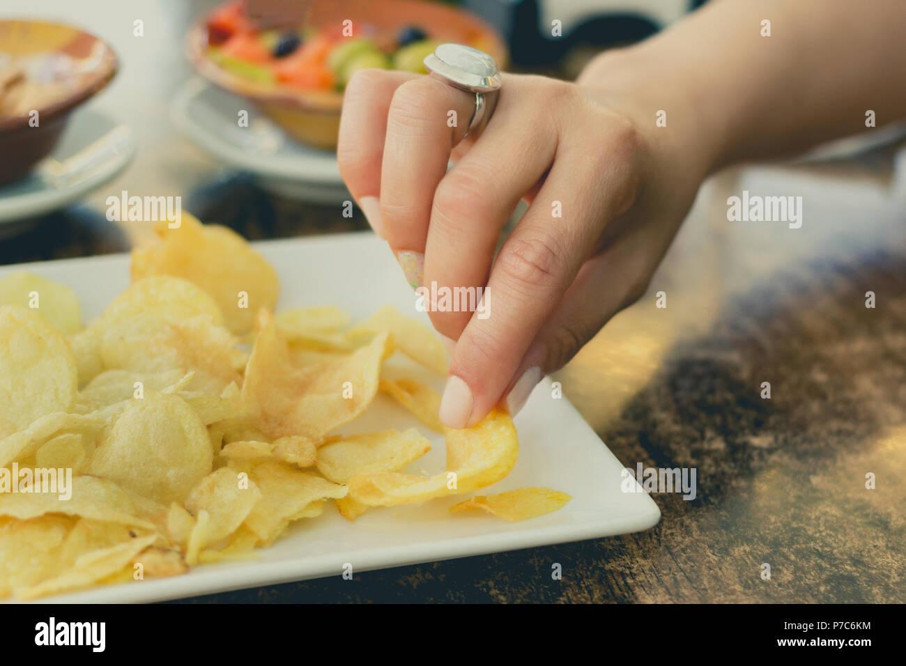 Las manos de una mujer recogiendo una papa frita durante un snack Imagen De Stock