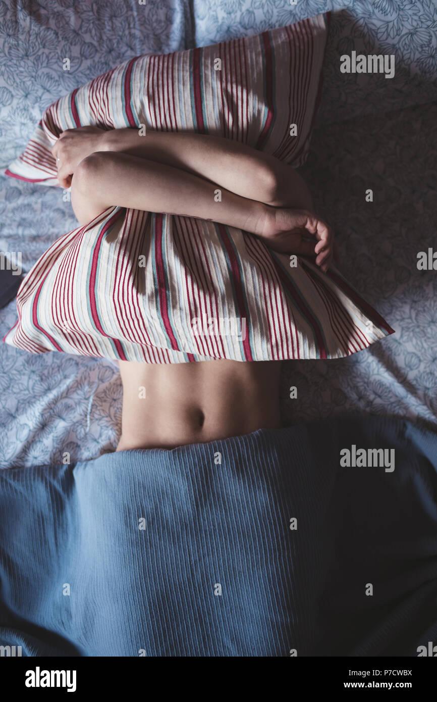 Mujer abrazando la almohada mientras duermen en el dormitorio Imagen De Stock
