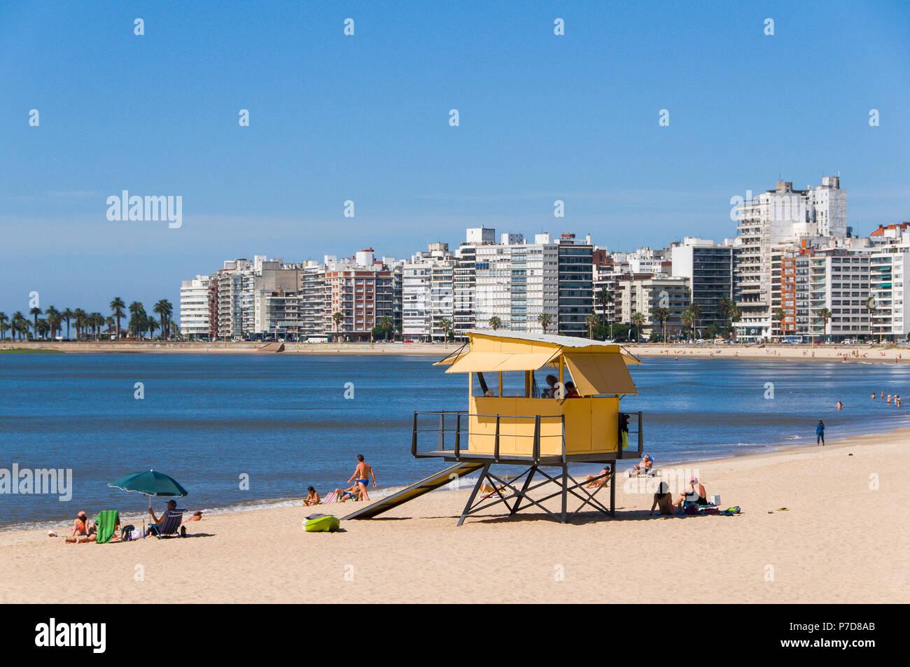 Bañistas en la playa de la ciudad, la torre de socorrista y rascacielos en Montevideo, Uruguay. Imagen De Stock