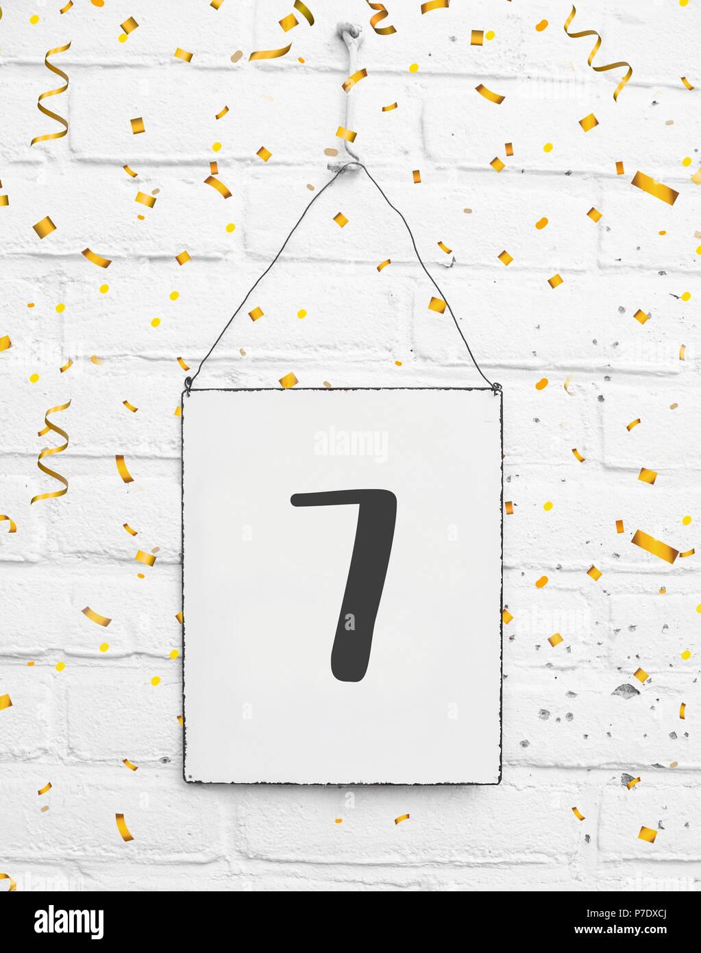 7 años fiesta de cumpleaños tarjeta golden confeti de texto con el número 7. Imagen De Stock