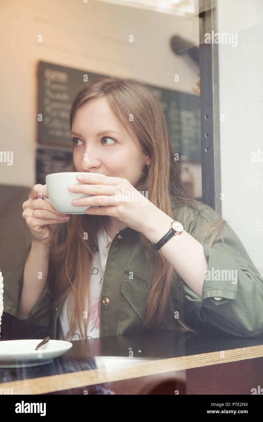 Mujer joven con café en el café Imagen De Stock