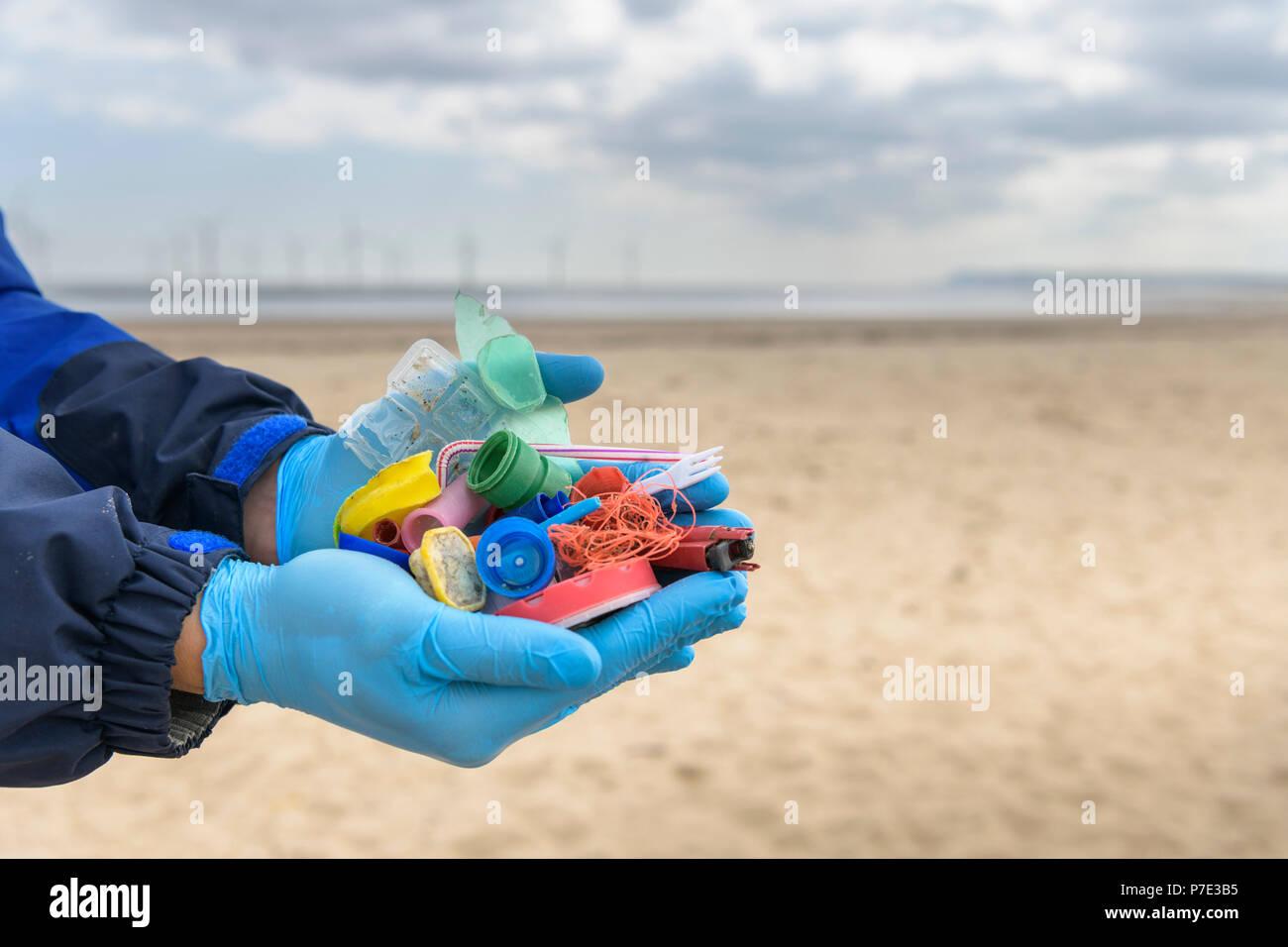 Hombre sujetando ejemplos de contaminación plástica recogidos en la playa, al Noreste de Inglaterra, Reino Unido. Foto de stock