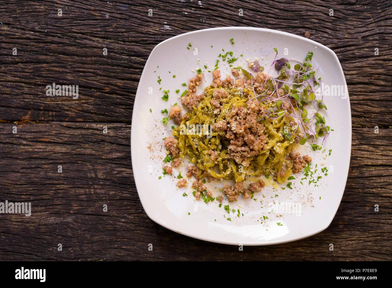 Tagliolini Pasta con pesto y salchichas. Imagen De Stock