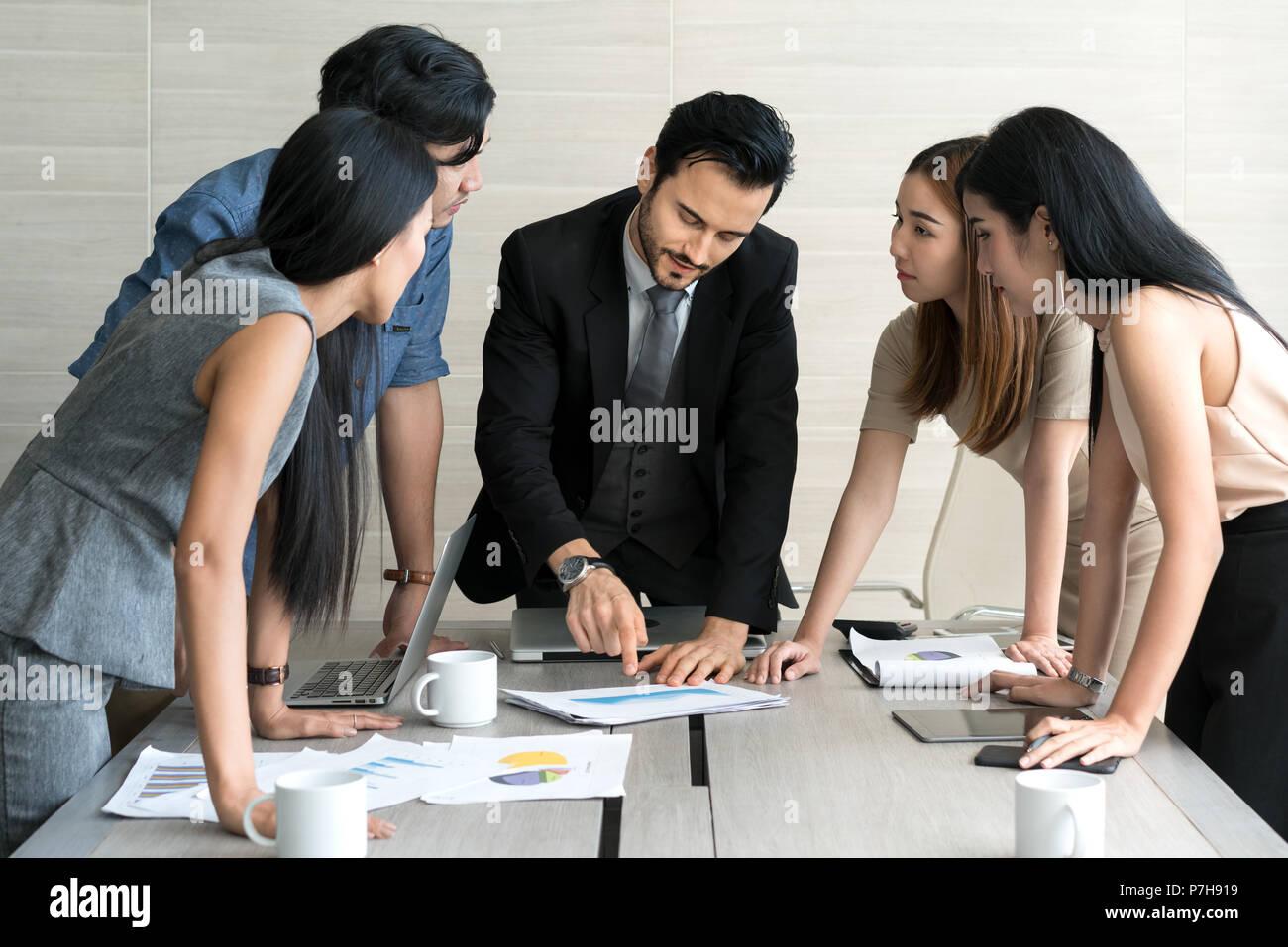 Smart manager explicando la reunión interna a su equipo de proyectos en la oficina moderna. La persona de negocios grupo multiétnico en traje. Proyecto y empresa c Foto de stock
