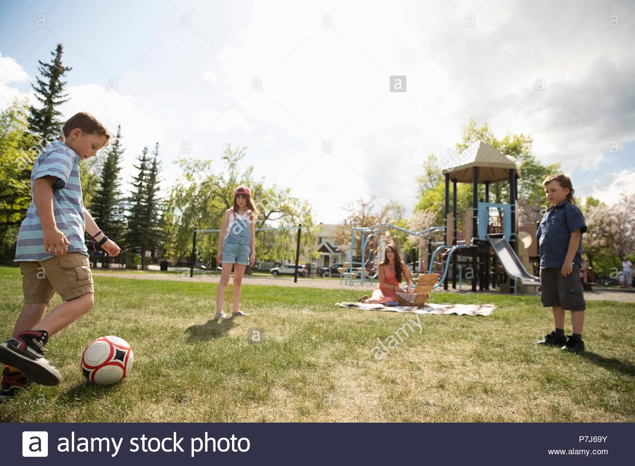 Madre en manta para picnic viendo niños jugando al fútbol en el parque soleado Imagen De Stock