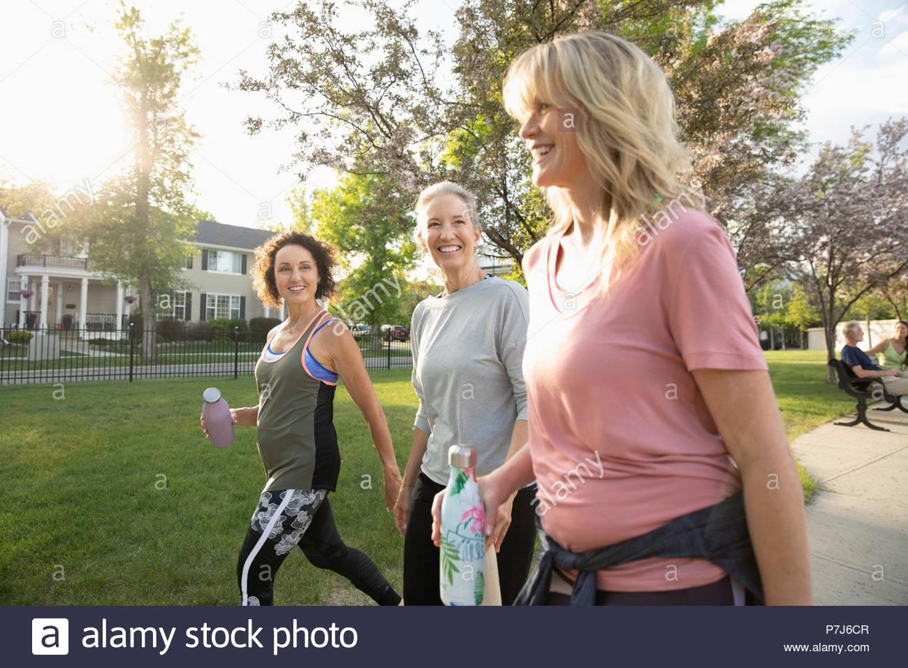 Las mujeres senior sonriente caminando, ejerciendo en sunny park Imagen De Stock