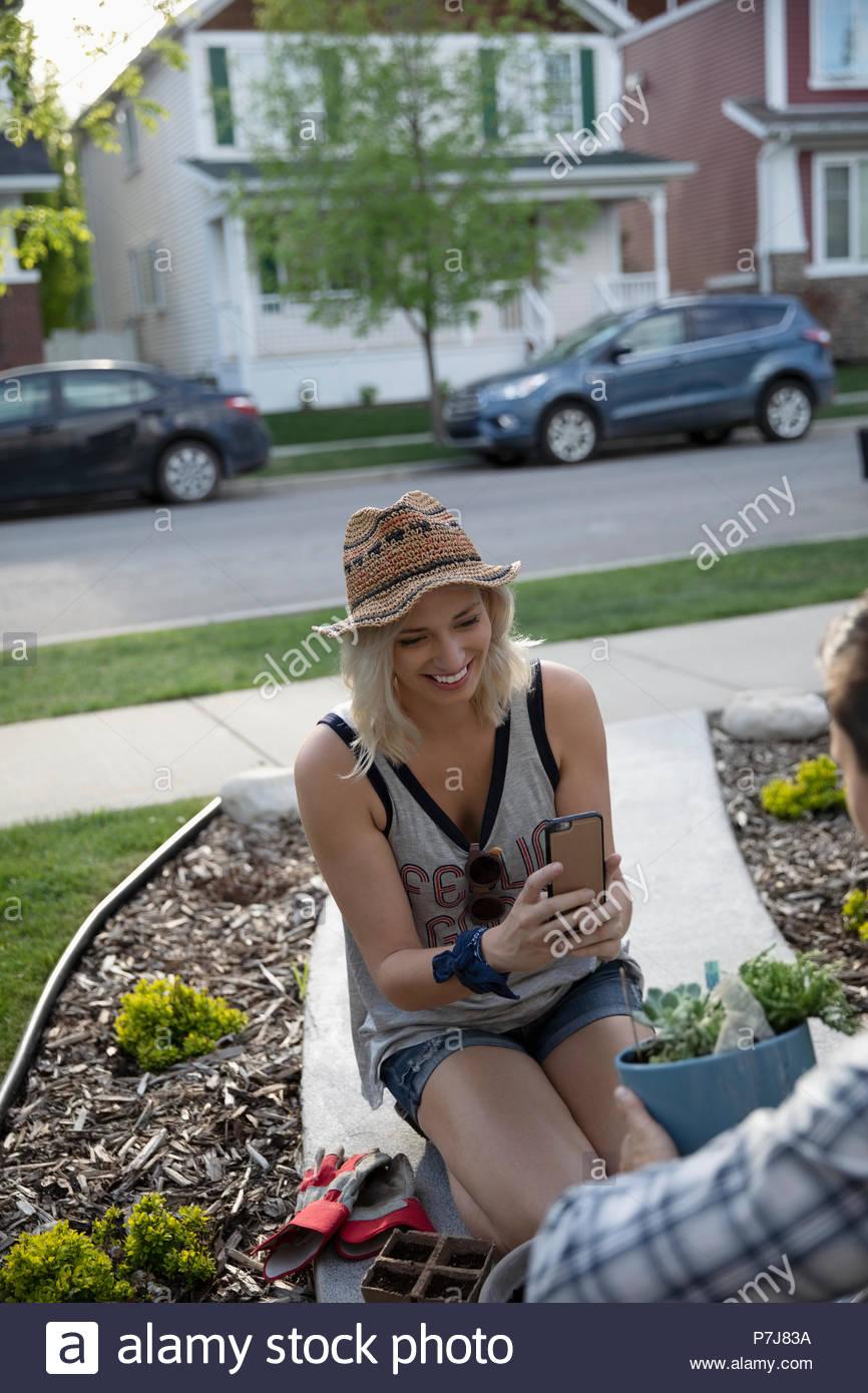 Mujer sonriente jardinería, fotografiando el marido la celebración de planta en maceta Imagen De Stock