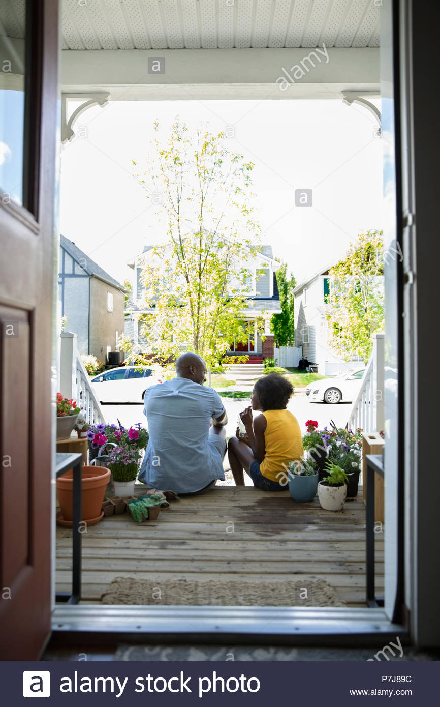Padre e hija pegado, plantar flores en la parte delantera stoop Imagen De Stock