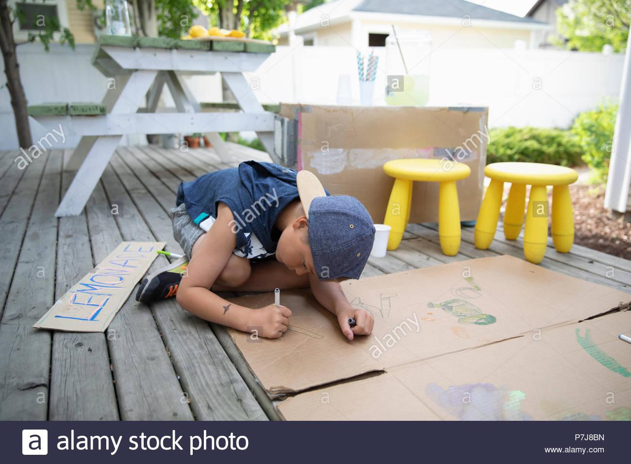 Dibujo de muchacho sobre cartón, haciendo Lemonade Stand Imagen De Stock
