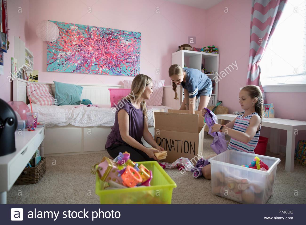 Madre y sus hijas organizando dormitorio, donando Imagen De Stock