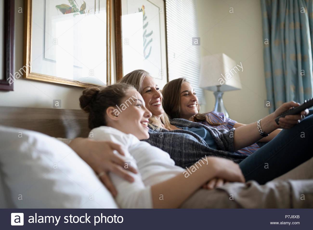 Madre afectuosa y hijas adolescentes viendo la televisión en la cama Imagen De Stock