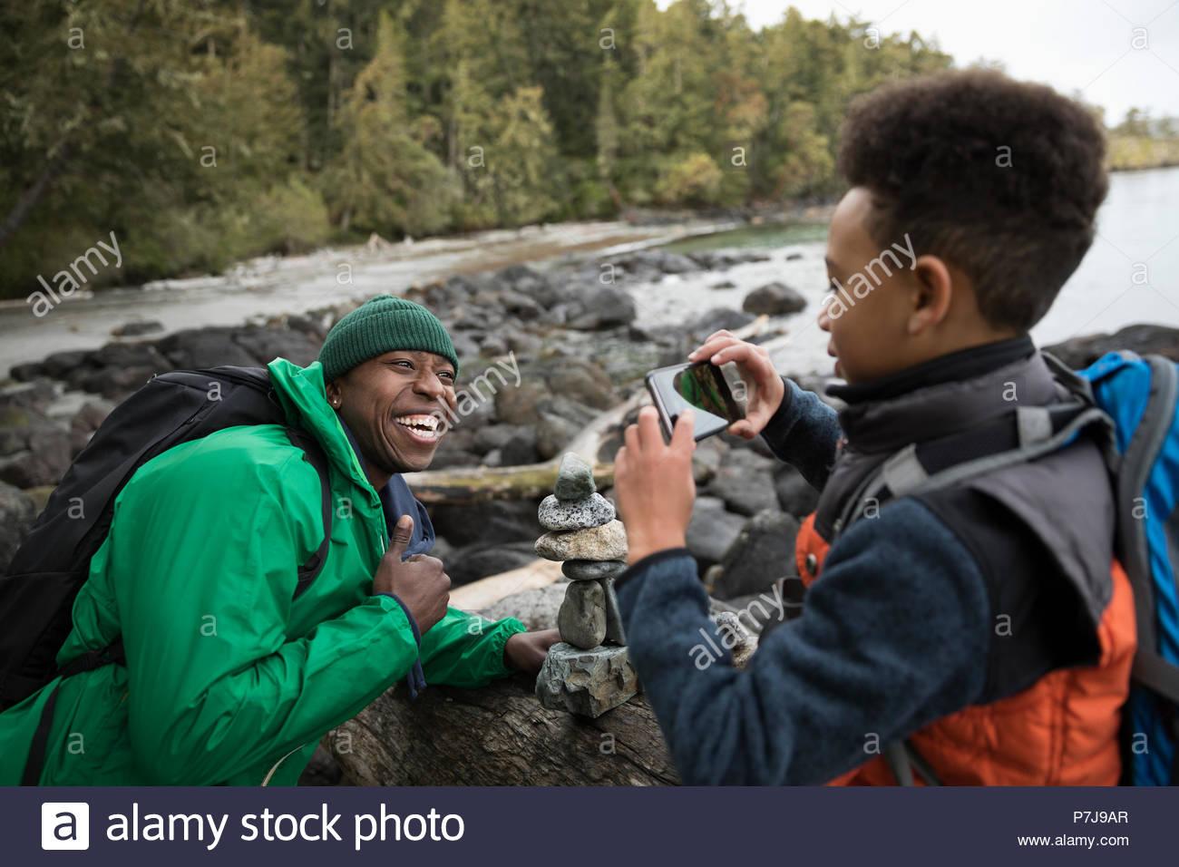 Hijo con cámara teléfono fotografiar juguetón padre en playa resistente Imagen De Stock