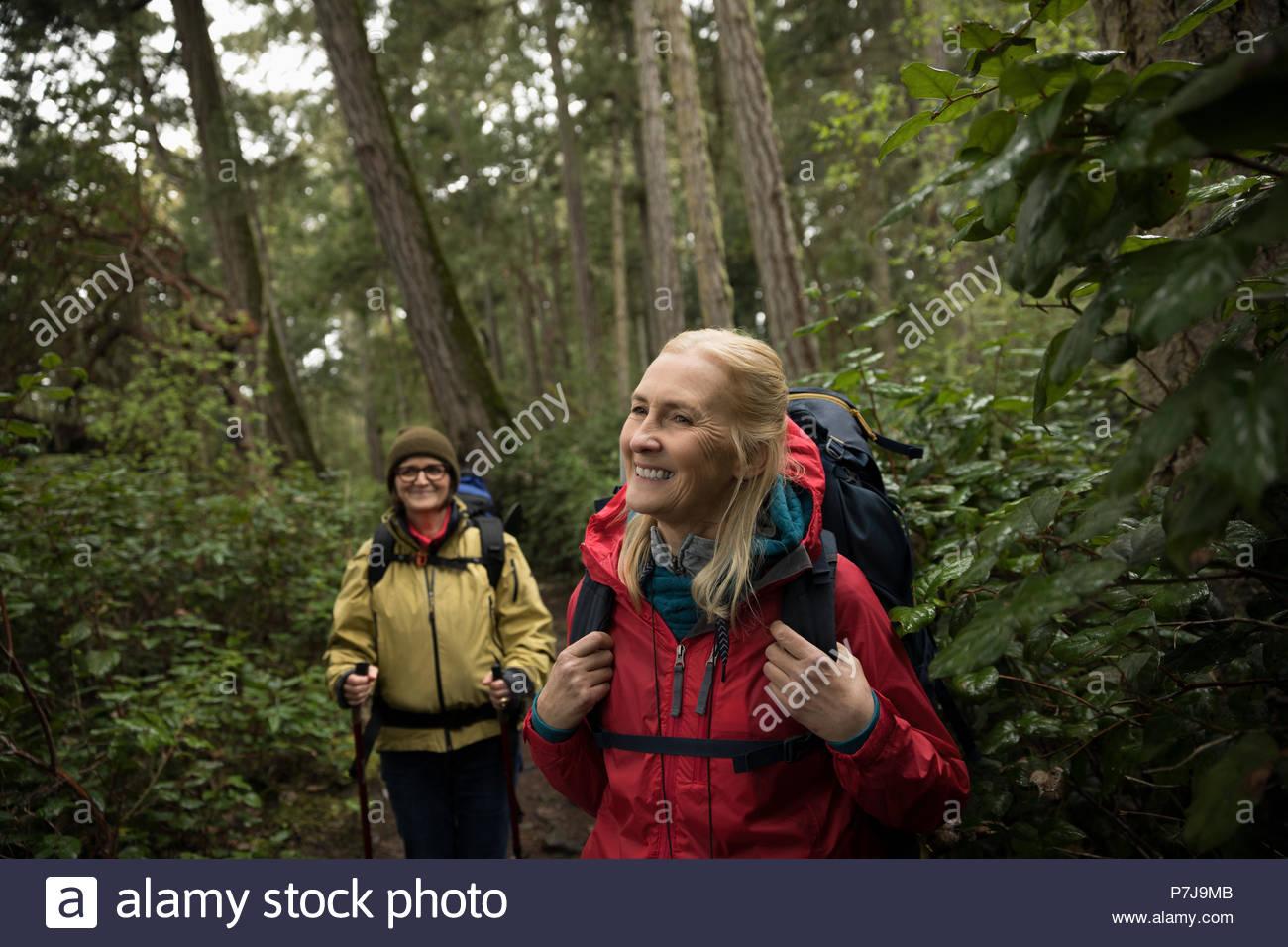 Sonriente, despreocupado senior activo mujeres excursionistas caminatas en el bosque Imagen De Stock