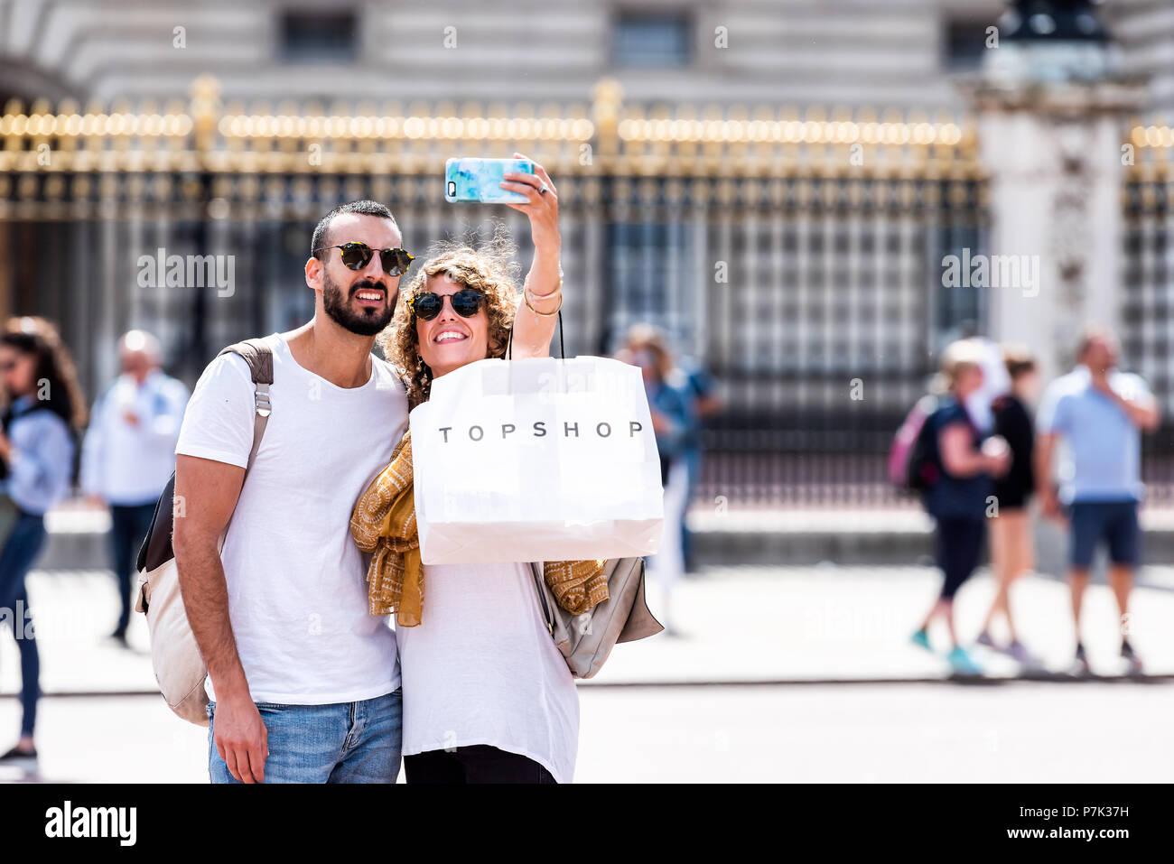 Londres, Reino Unido - 21 de junio de 2018: jóvenes románticas sonriendo feliz pareja teniendo selfie permanente delante de oro, Golden Buckingham Palace closeup valla, topsh Imagen De Stock