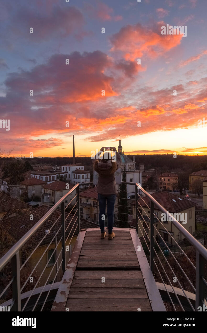 Un turist tomar una fotografía durante una puesta de sol en el balcón sobre el pueblo trabajador modelo de Crespi d'Adda, Sitio del Patrimonio Mundial de la Unesco. Capriate San Gervasio, provincia de Bérgamo, en Lombardía, Italia. Imagen De Stock