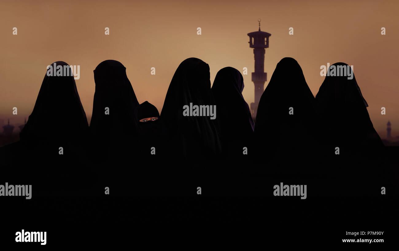 Silueta de la mujer musulmana y niña en atuendo musulmán, burka Imagen De Stock