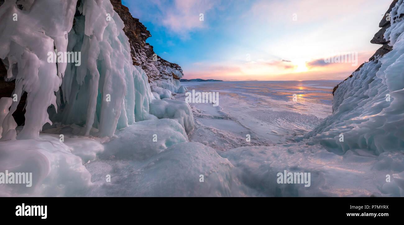 Una fotografía panorámica las estalactitas de hielo en una cueva en la orilla al atardecer en el lago Baikal, región de Irkutsk, Siberia, Rusia Imagen De Stock