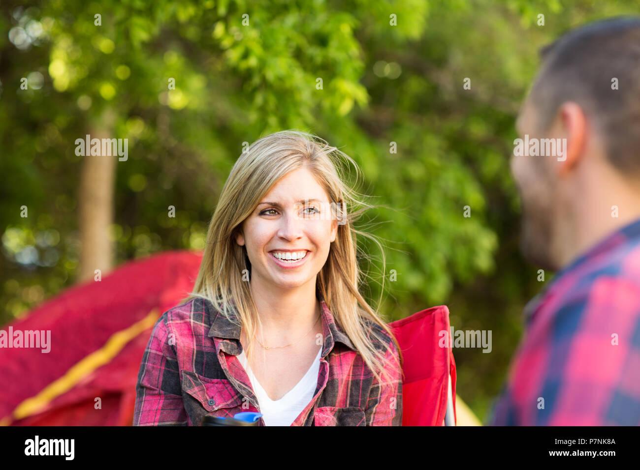 Par hablando y riéndose de camping. Imagen De Stock