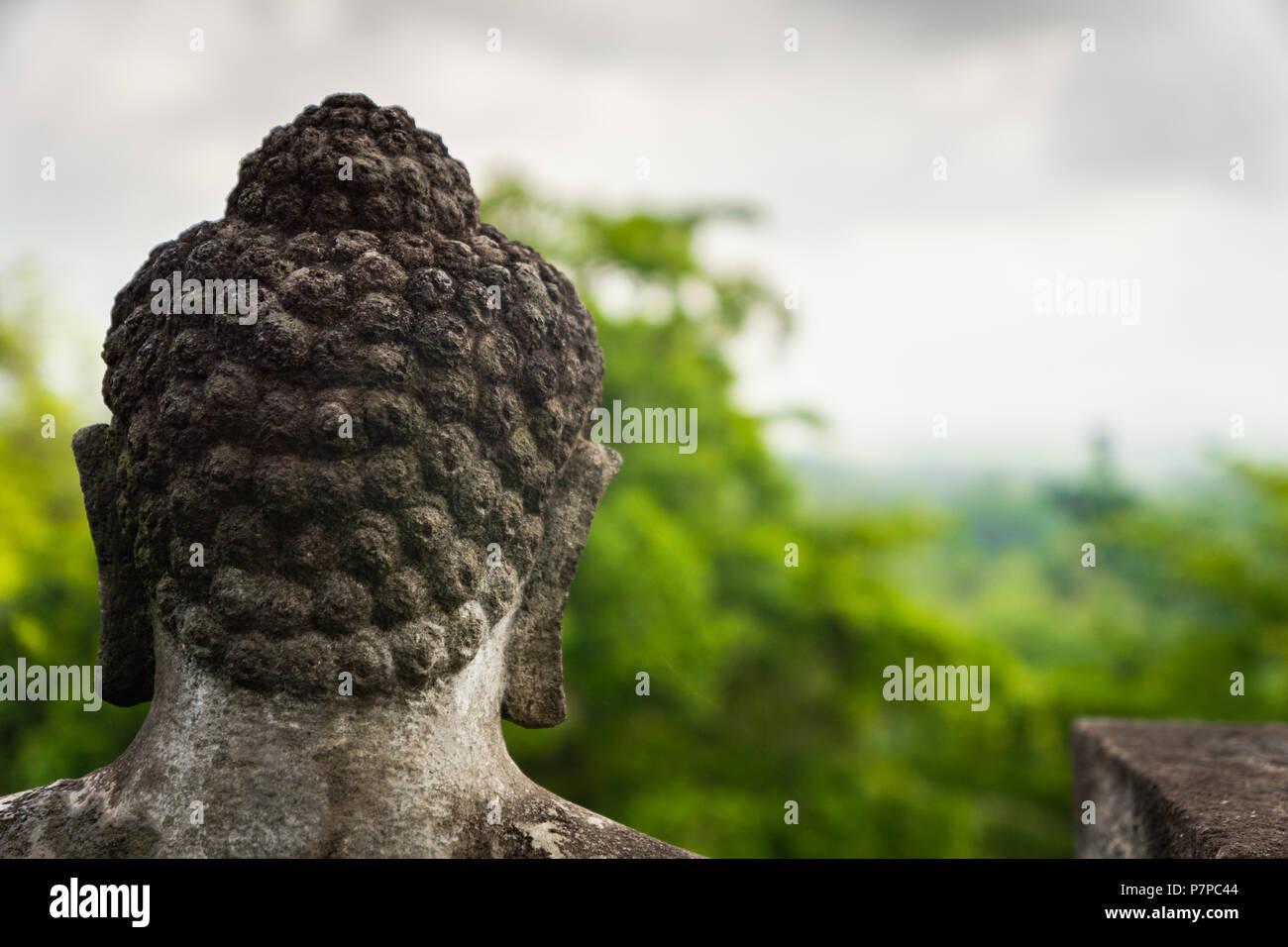 La parte posterior de la cabeza de una estatua de Buda mirando el Templo Borobudur en Indonesia. Imagen De Stock