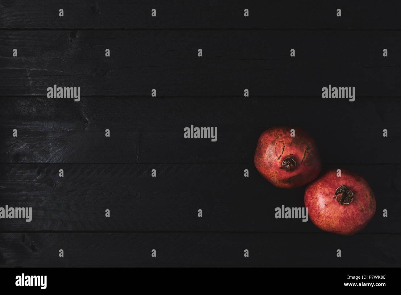 Plano de laicos maduros de fruta de granada sobre fondo negro vintage de madera. Vista superior con espacio de copia. Imagen De Stock