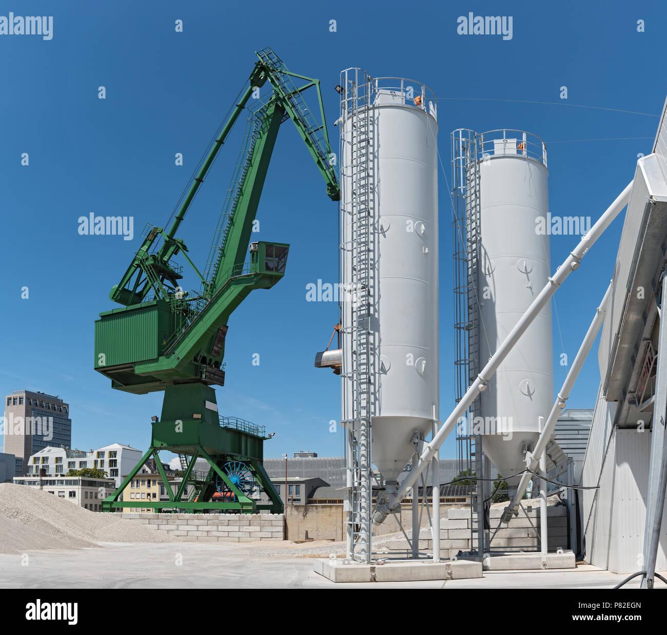 Vista exterior de una fábrica de cemento con grúa verde. Imagen De Stock