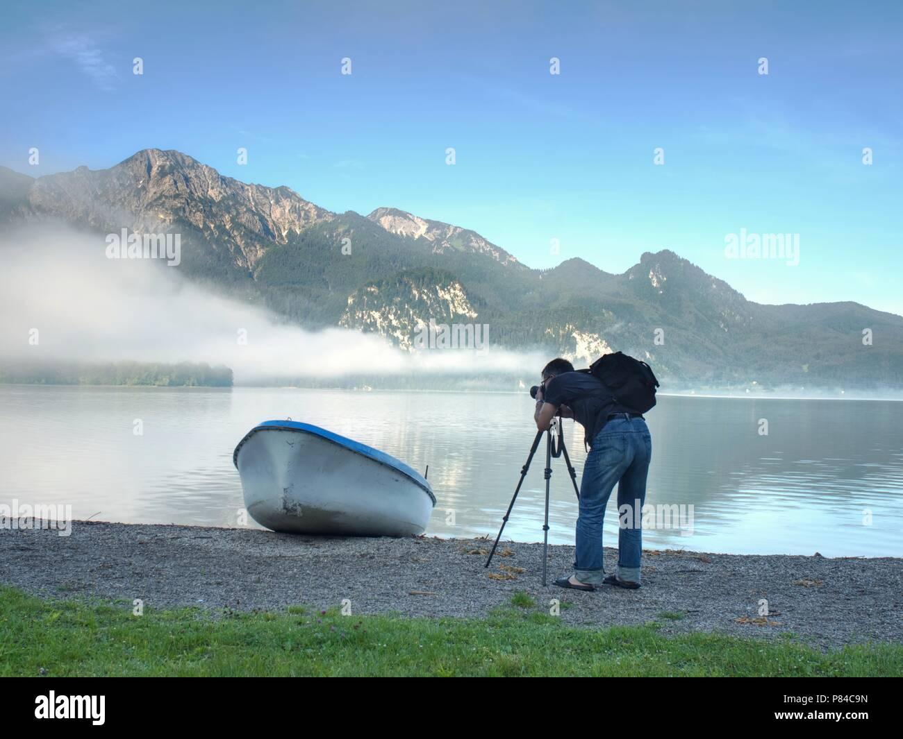 El hombre caminante se toma de fotografía de barco en la orilla del lago de montaña. Silueta en botes de pesca en el lago costa. Imagen De Stock
