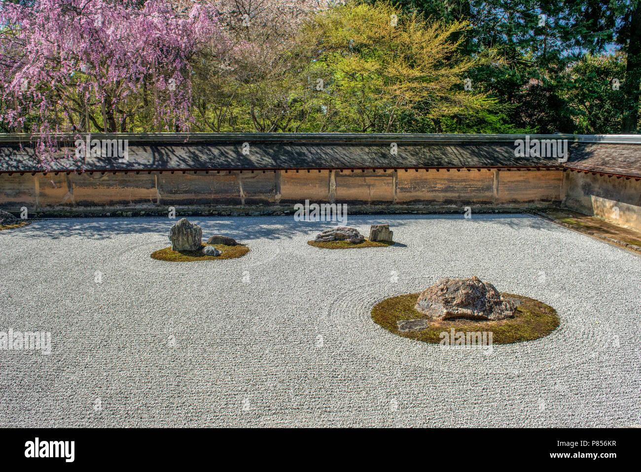 Los turistas japoneses disfrutan de la tranquilidad en el Templo Ryoanji en Kyoto, Japón. Este templo Budista Zen es famoso por su jardín de rocas. Imagen De Stock