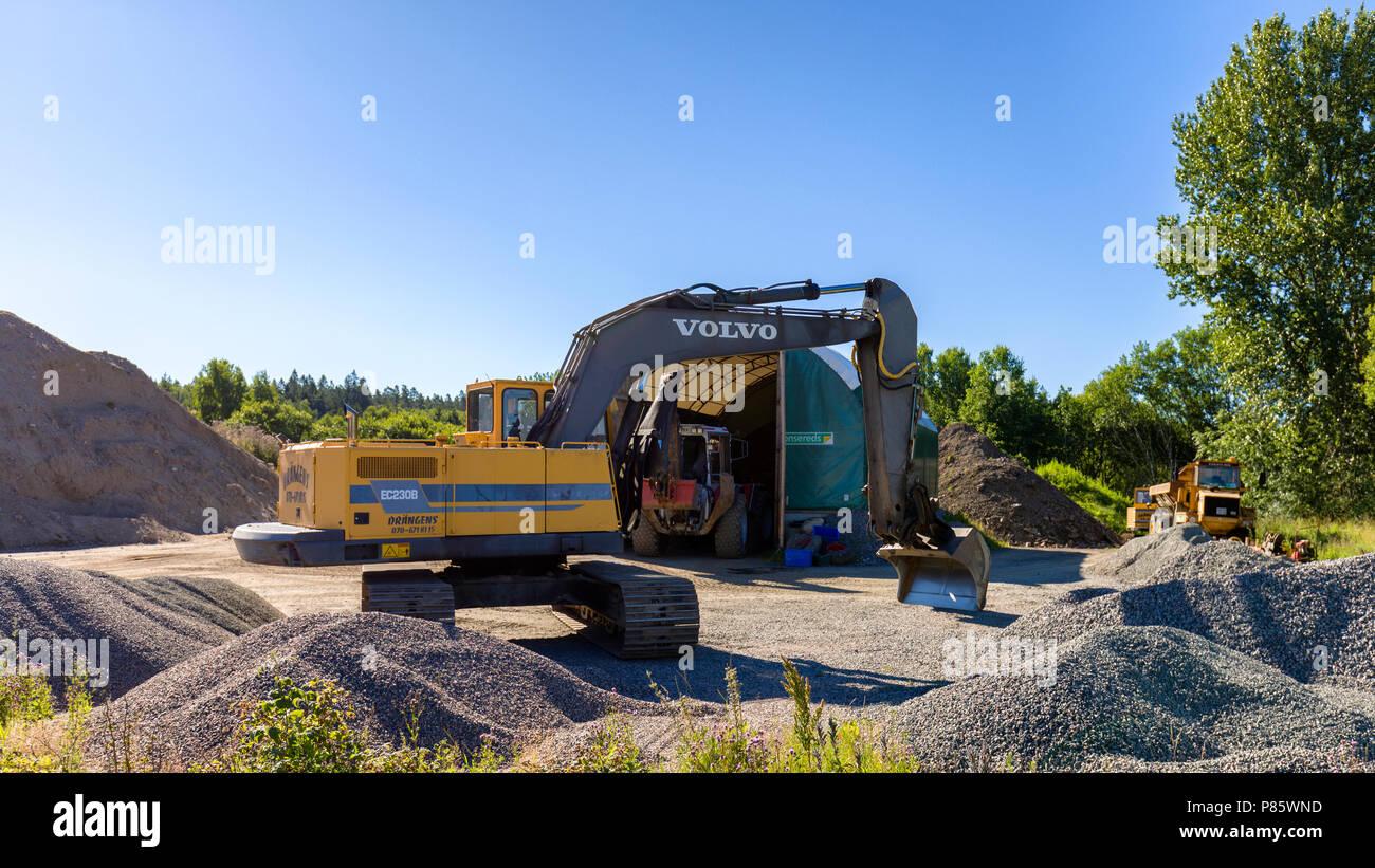 Excavadora articulados en medio de los grandes montones de agregados de construcción Imagen De Stock