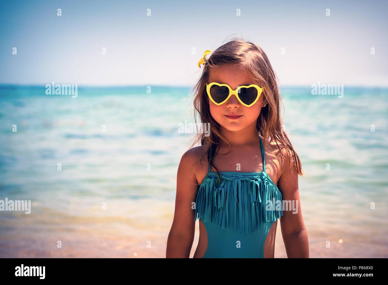Retrato de una linda niña en la playa, el encanto de un niño llevaba elegante bañador y gafas de sol en forma de corazón, moda bebé, felices vacaciones de verano Imagen De Stock