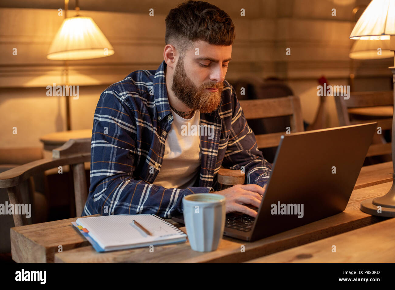 Joven Profesional navegando por Internet en su ordenador portátil en un café Imagen De Stock