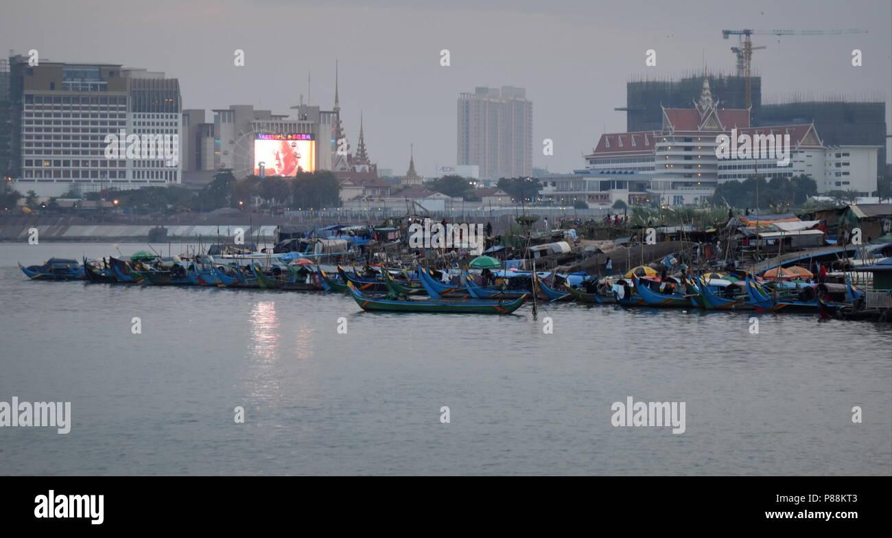 Horizonte de Phnom Penh: el contraste del paisaje urbano en construcción y los barcos de pesca y la pobreza de las minorías musulmanas a lo largo del río Mekong Foto de stock