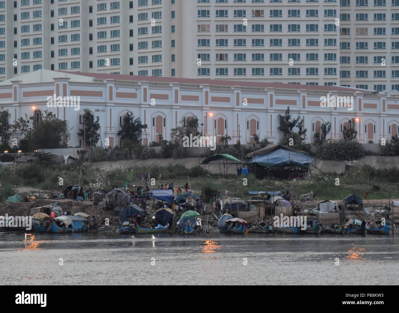 Contraste de hoteles de lujo y barcos de pesca y la pobreza de las minorías musulmanas a lo largo del río Mekong en Phnom Penh, Camboya Imagen De Stock