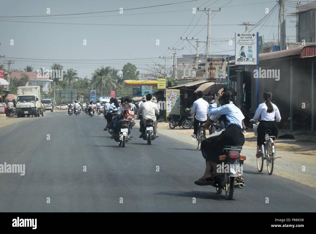 Las zonas rurales de Camboya escuela estudiantes viajan de regreso a casa con las bicicletas y motocicletas en la vía pública Foto de stock