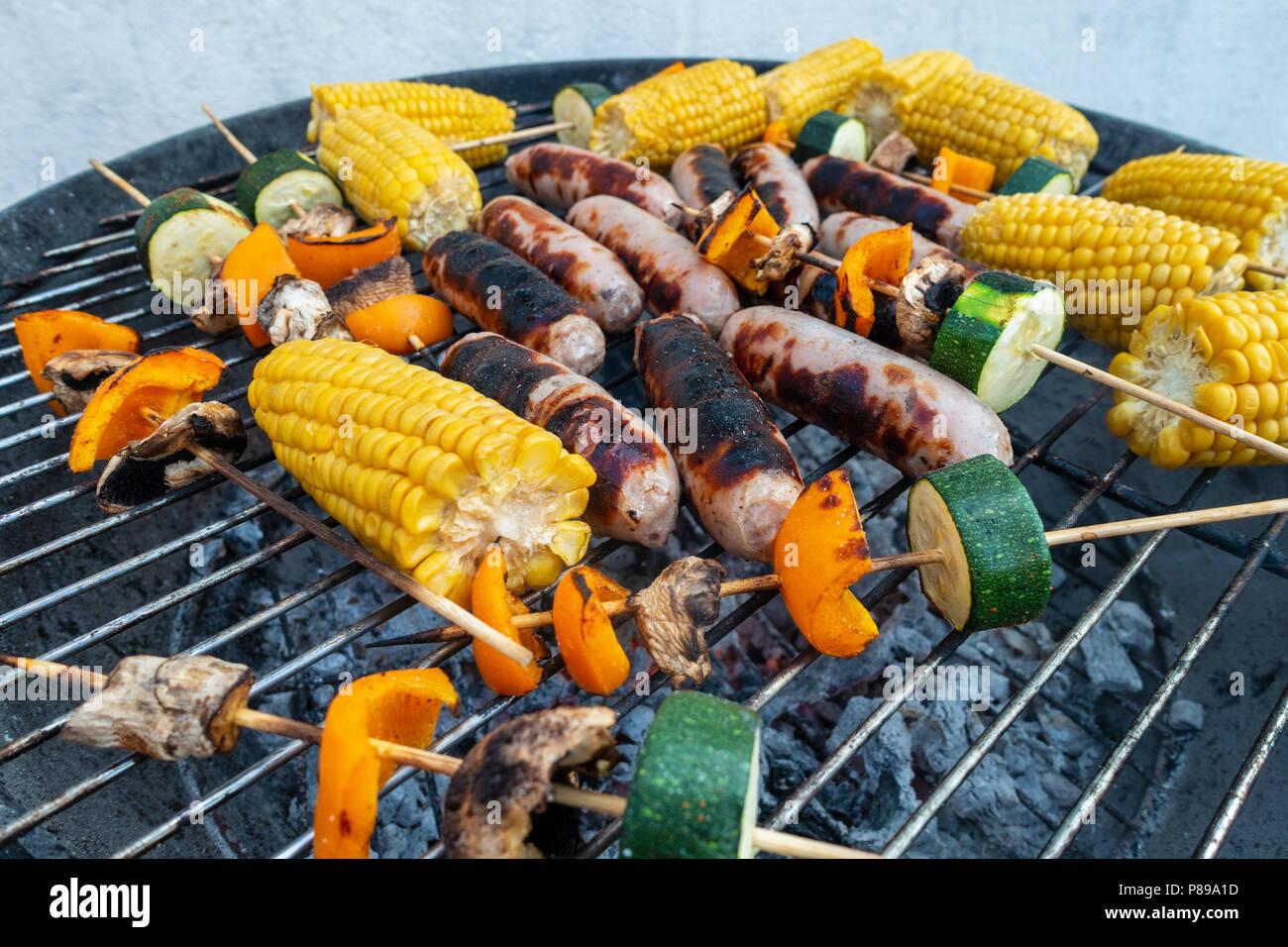 Los embutidos, la mazorca de maíz y hortalizas kebabs de setas, pimiento y calabacín cocinar fuera en una barbacoa. Imagen De Stock