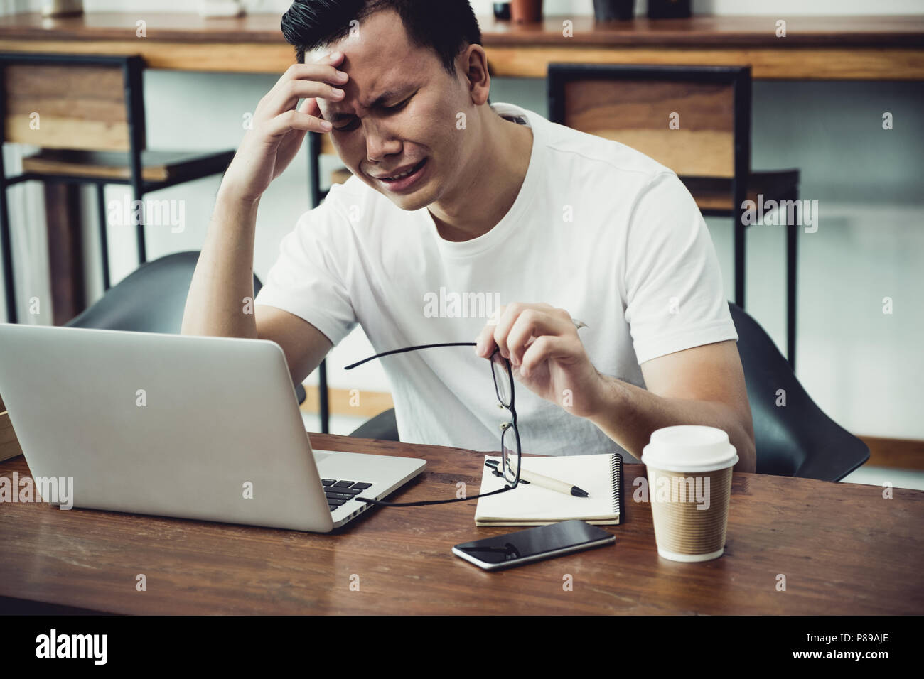 Asia hombre casual cara cubierta con malestar de mano de obra en la parte frontal del ordenador portátil en la cafetería,estrés concepto emoción,trabajo fuera de la oficina,trabajo en hom Imagen De Stock